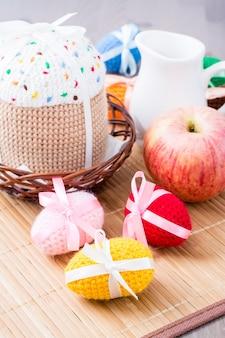 Oeufs de pâques tricotés et gâteau dans un panier et pichet sur une table en bois