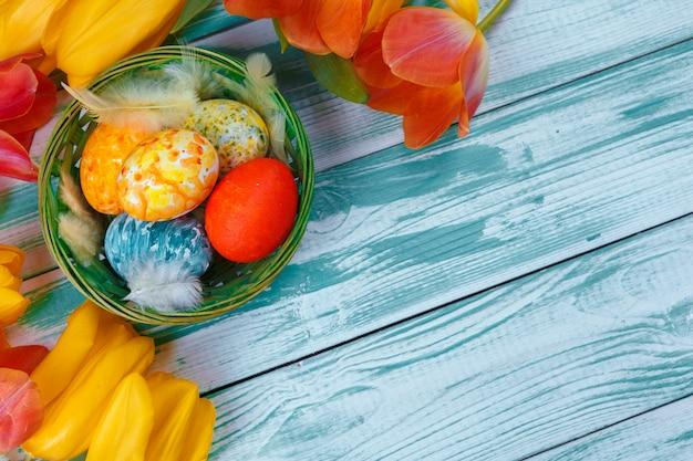 Oeufs de pâques avec des tulipes sur un fond en bois bleu
