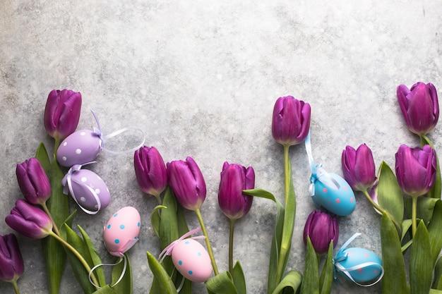Oeufs de pâques et tulipes lilas vue de dessus à plat
