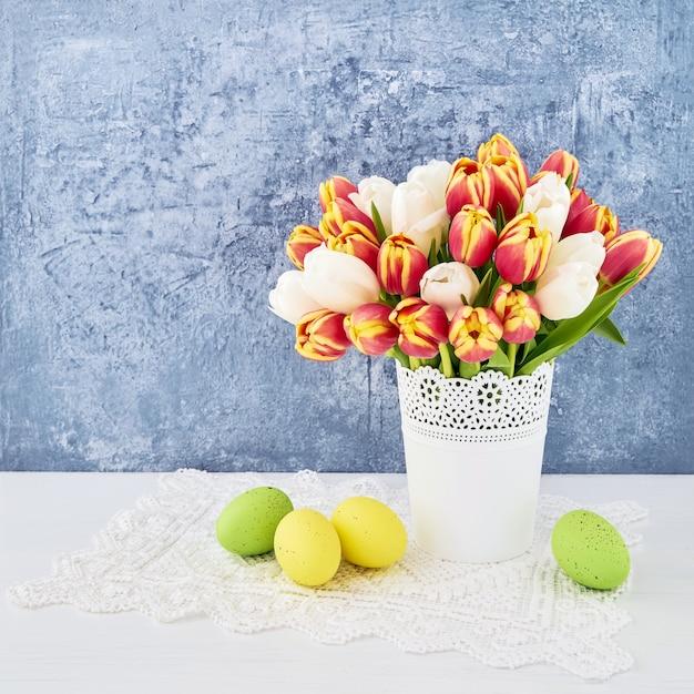 Oeufs de pâques et tulipes rouges dans un vase. copiez l'espace. concept de célébration de pâques.