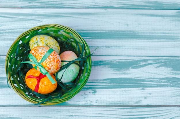 Oeufs de pâques avec des tulipes sur une table en bois bleue