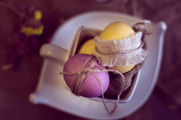 Oeufs de pâques violets et jaunes dans une tasse sur toile de jute
