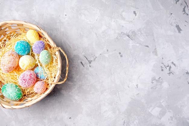 Oeufs pastel bleu vert rose dans le panier sur fond gris avec un espace pour le texte. joyeuses pâques.