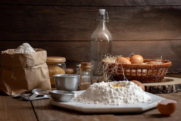 Oeufs, pâte et farine sur une table en bois avec splat background pour un objet dans une boulangerie