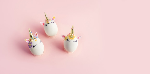 Oeufs peints avec le thème de la licorne sur une surface rose. concept de pâques