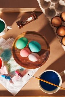 Oeufs, peintures colorées, pinceaux, crayons sur fond de bois, oeufs à colorier, préparation pour pâques, vacances saisonnières de printemps