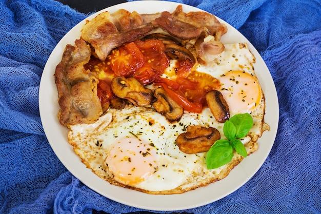 Œufs sur le plat avec bacon, tomates et champignons sur une surface sombre. vue de dessus