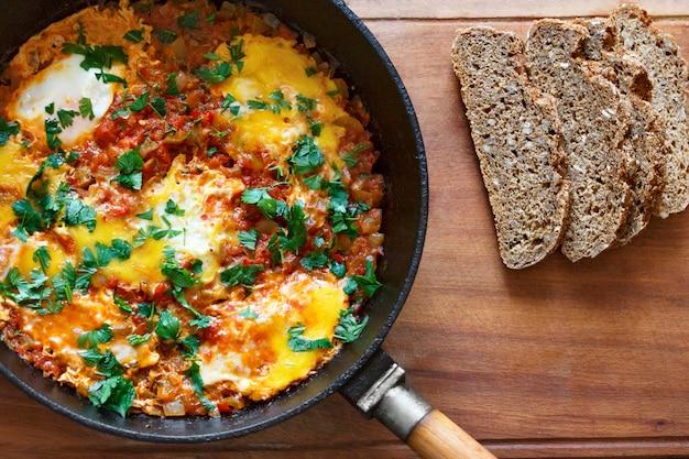 Œufs sur le plat dans une poêle avec du pain aux céréales. shakshuka vue d'en haut.
