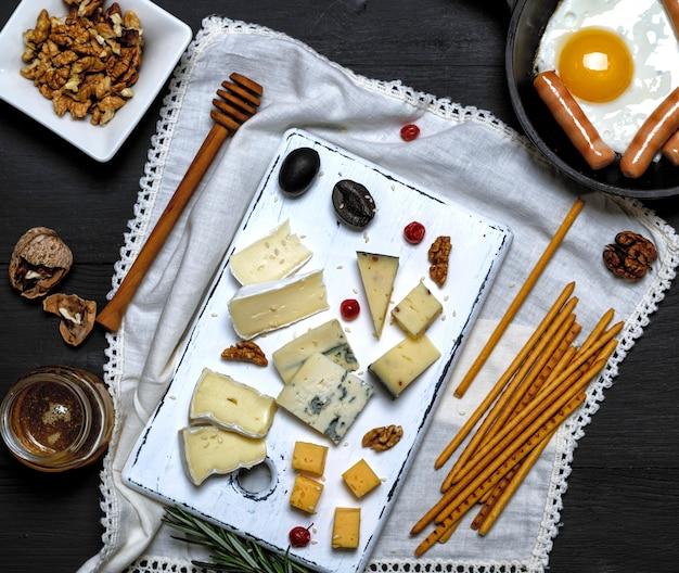 Œufs sur le plat avec des saucisses dans une poêle à frire noire et du fromage