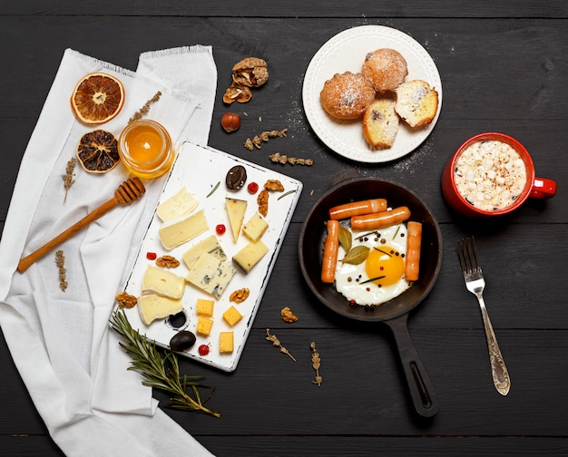Œufs sur le plat avec des saucisses dans une poêle à frire ronde et un plateau de fromages