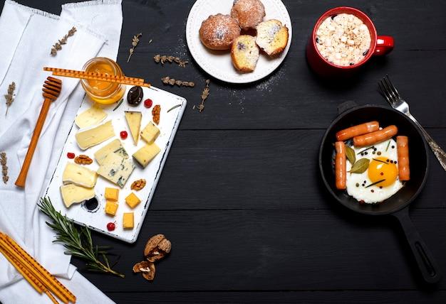 Œufs sur le plat avec des saucisses dans une poêle à frire et des types de fromage