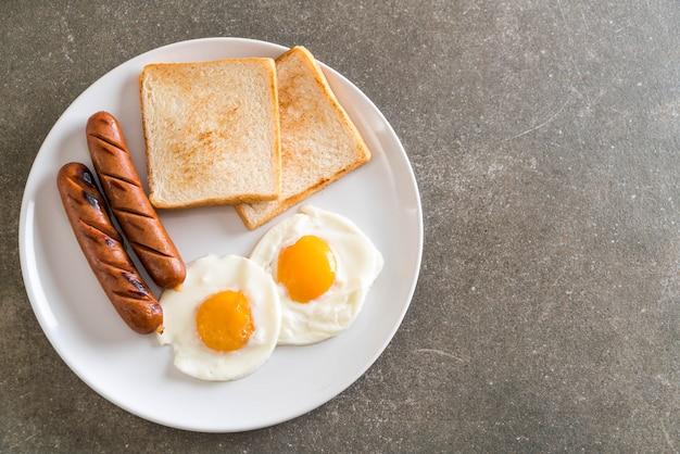 œufs sur le plat avec des saucisses et du pain