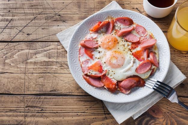 Oeufs sur le plat saucisses et tomates sur une assiette sur la table.