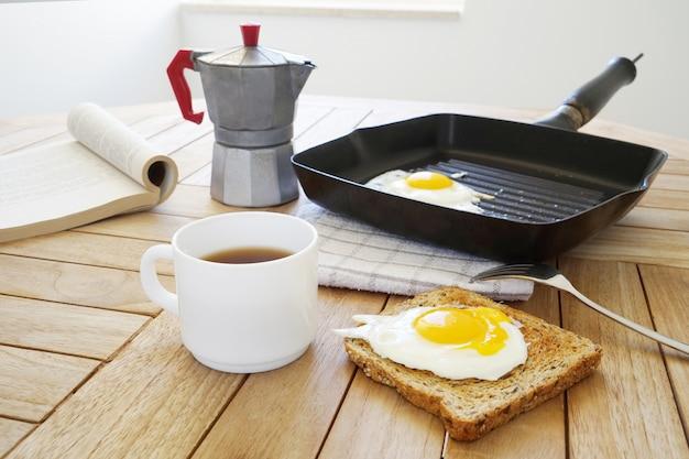Œufs sur le plat avec toast, livre ouvert, une tasse de café et une machine à café à geyser sur une table en bois