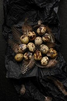 Oeufs et plumes de caille sur papier d'emballage froissé noir. beaucoup de petits œufs tachetés sur un fond noir texturé. nourriture saine.