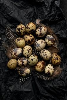 Oeufs et plumes de caille sur papier d'emballage froissé noir.