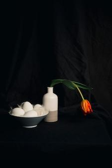 Œufs et plumes près d'une fleur d'oranger fanée dans un vase