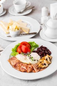 Oeufs pochés aux légumes, jambon, tomates, haricots rouges et pain au levain isolé sur une table en marbre blanc. nourriture faite maison. petit déjeuner savoureux. mise au point sélective.
