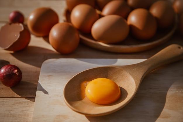 Les œufs pondent sur des plateaux en bois et ont des œufs cassés.