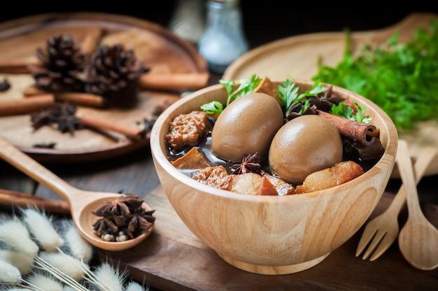 Les oeufs et le porc bouilli dans la sauce sur une table en bois.