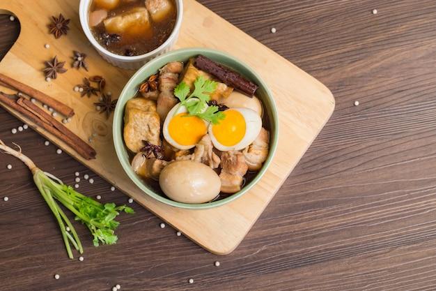 Oeufs et porc sucré avec du tofu frit, bouilli dans une sauce brune et dans un bol blanc.