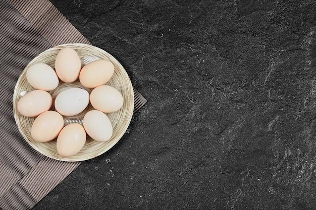 Œufs de poule sur une assiette en céramique. vue d'en-haut.