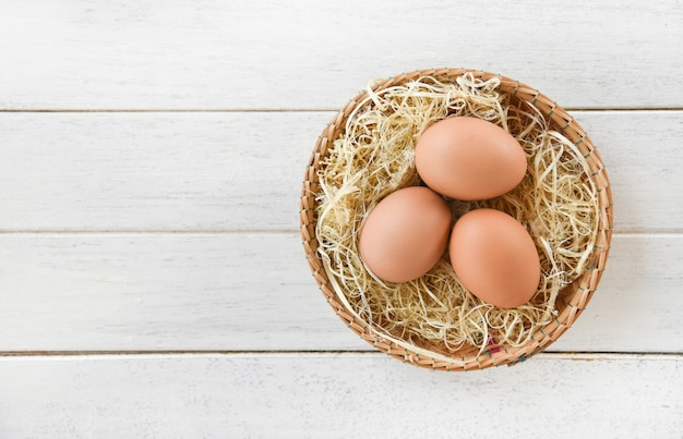 Œufs de poule au panier nid sur une table en bois