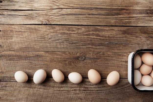 Oeufs de poule bio dans une boîte en métal sur fond de bois d'affilée. concept de ménage biologique avec des œufs de poules élevées en plein air et en pâturage