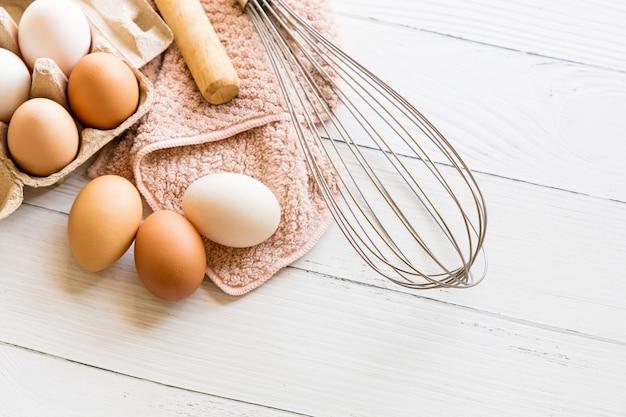 Oeufs de poule bio dans des boîtes en papier brun, fouet et rouleau à pâtisserie placés sur une table en bois blanc. matières premières et équipement pour faire du pain maison.vue de dessus et espace de copie