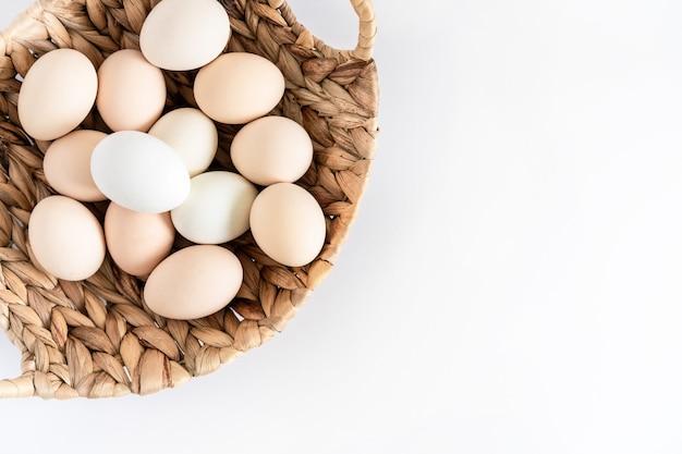 Oeufs de poule bio ferme crue fraîche dans un panier sur fond blanc.
