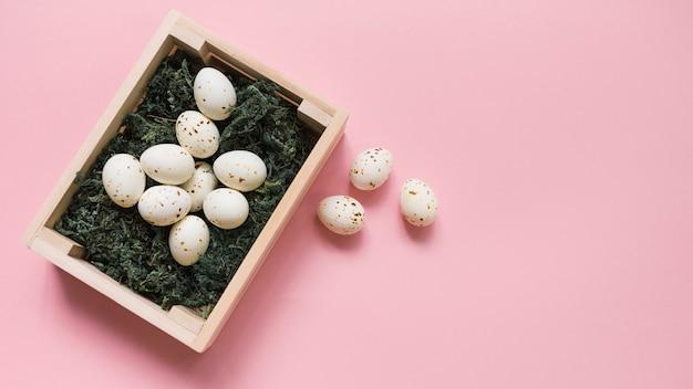 Œufs de poule blanche en boîte sur table rose