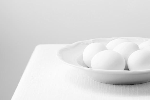 Œufs de poule blancs à angle élevé sur assiette