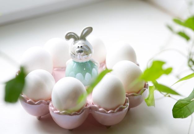 Oeufs de poule blancs sur un beau support décoratif avec un lièvre en céramique