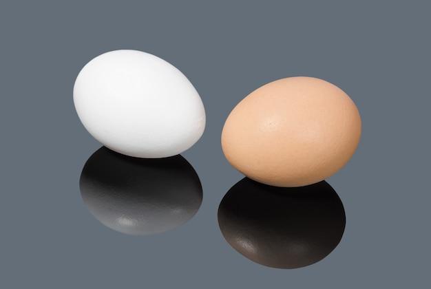Oeufs de poule blancs et bruns sur fond gris
