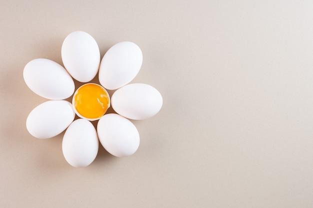 Oeufs de poule blancs crus frais placés sur une table beige.