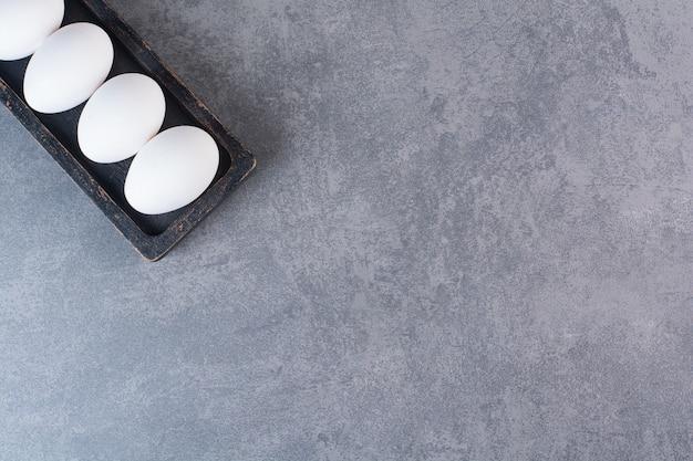 Oeufs de poule blancs crus frais placés sur une table en pierre.