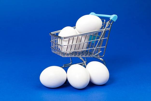 Oeufs de poule blancs dans un panier.