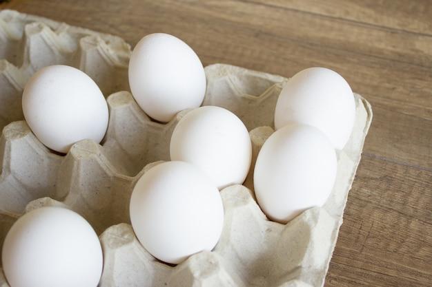 Œufs de poule blancs dans un plateau en carton