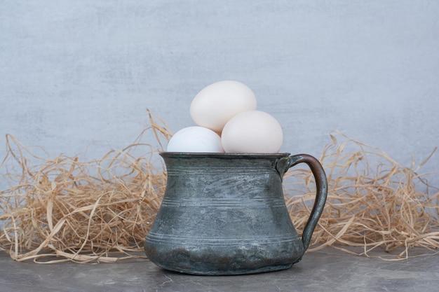 Oeufs de poule blancs frais dans une ancienne tasse sur du foin. photo de haute qualité