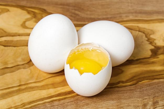Oeufs de poule blancs et oeufs cassés sur planche ou table en bois.