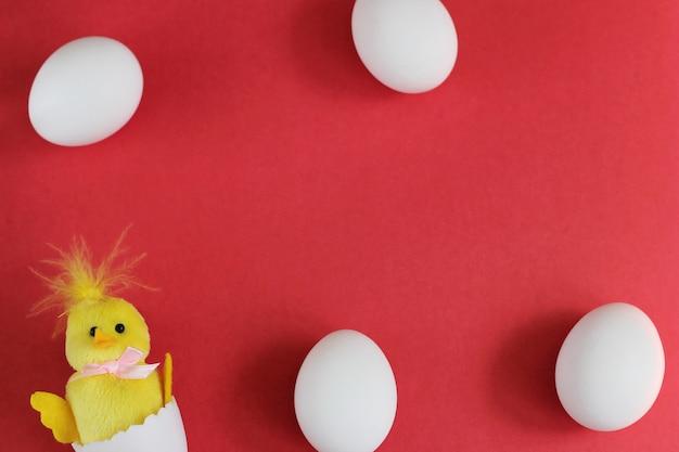 Oeufs de poule blancs et poulet jouet jaune sur fond rouge