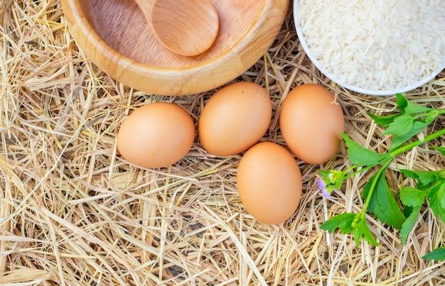 Œufs de poule de bonne qualité avec un bol en bois, du riz cru et des légumes.