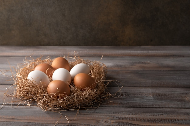 Oeufs de poule brun et blanc dans un nid de paille sur fond de bois. style rustique. copier l'espace