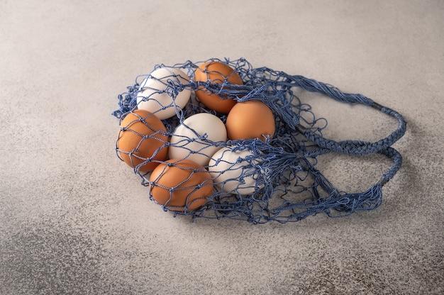 Oeufs de poule bruns et blancs dans un sac de ficelle sur un fond texturé clair.