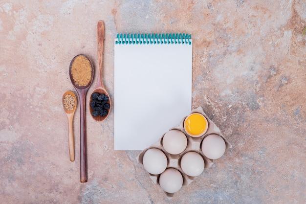 Oeufs de poule et cahier sur une surface en marbre.