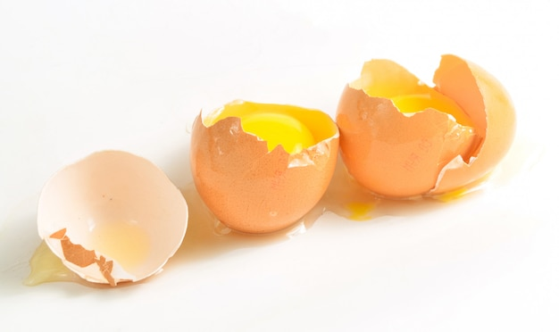 Oeufs de poule cassés isolés sur une surface blanche