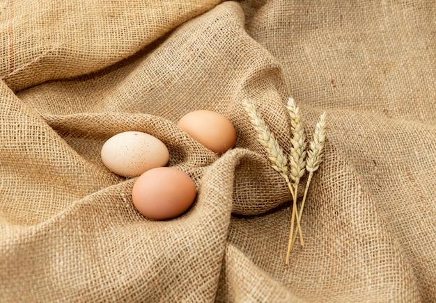 Œufs de poule et céréales sur un sac en toile