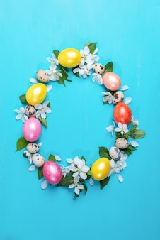 Oeufs de poule colorés, oeufs de caille et fleurs de pommier blanc disposées comme oeuf de pâques sur fond de bois peint turquoise.