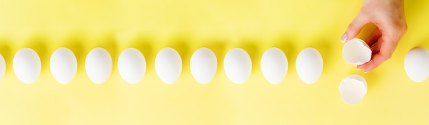 Œufs de poule crus blancs allongés en ligne sur une table à la mode jaune et main féminine tient un œuf cassé. composition créative minimale de pâques. vue de dessus.