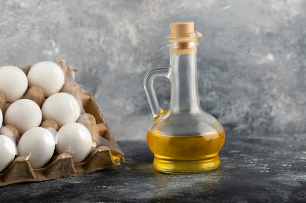 Œufs de poule crus dans une boîte à œufs avec une bouteille en verre d'huile.